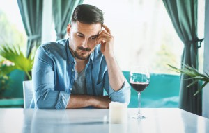 Closeup of early 30's man having some wine in the middle of the day and thinking about his relationship problem. Somewhere at the bottom of the glass there is a meaning of everything that bothers him right now.